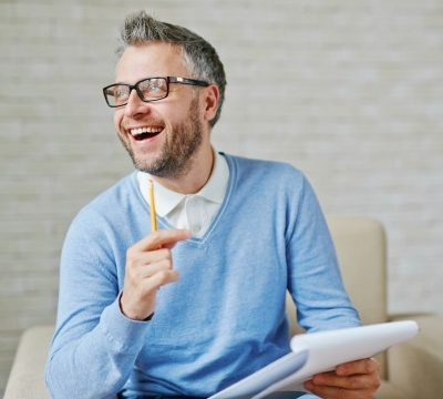 Happy psychiatrist with pencil and clipboard sitting in armchair